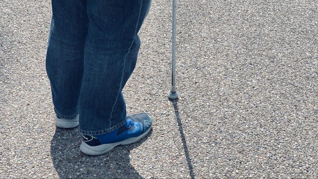 白杖を持って立つ渡辺さんを足元だけ撮影した画像