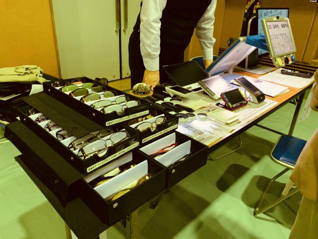 机の上に遮光眼鏡や拡大読書器が置かれている画像