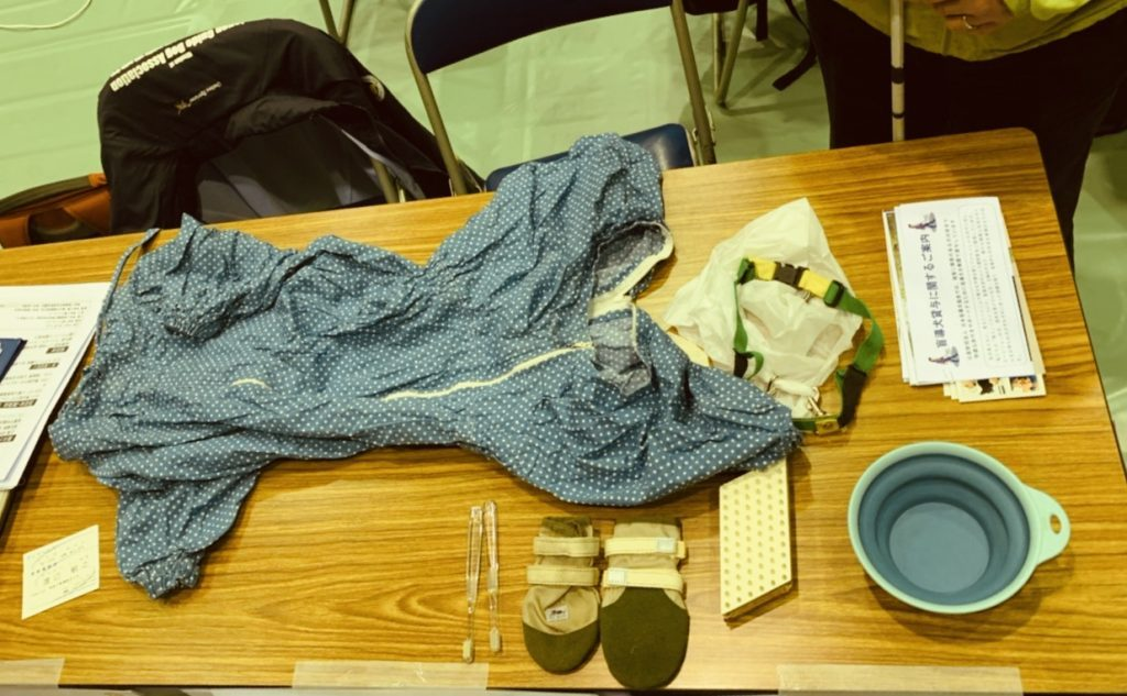 盲導犬の洋服やトイレ用のベルト、水を飲む容器などが机の上に並んでいる画像
