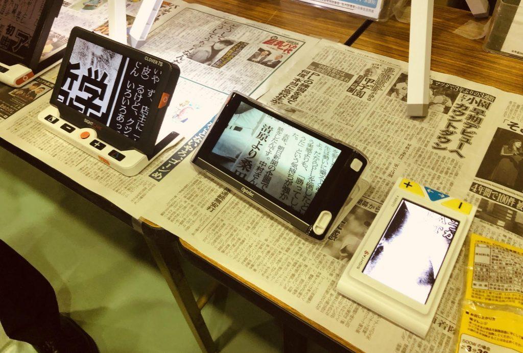 拡大読書器が机の上に3台あり、新聞を拡大している画像
