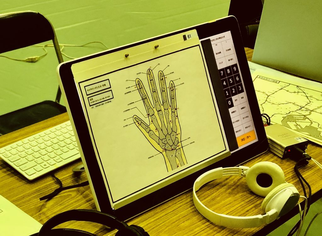 手のひらのツボを音声で確認できるデモ機が机の上に置かれている画像