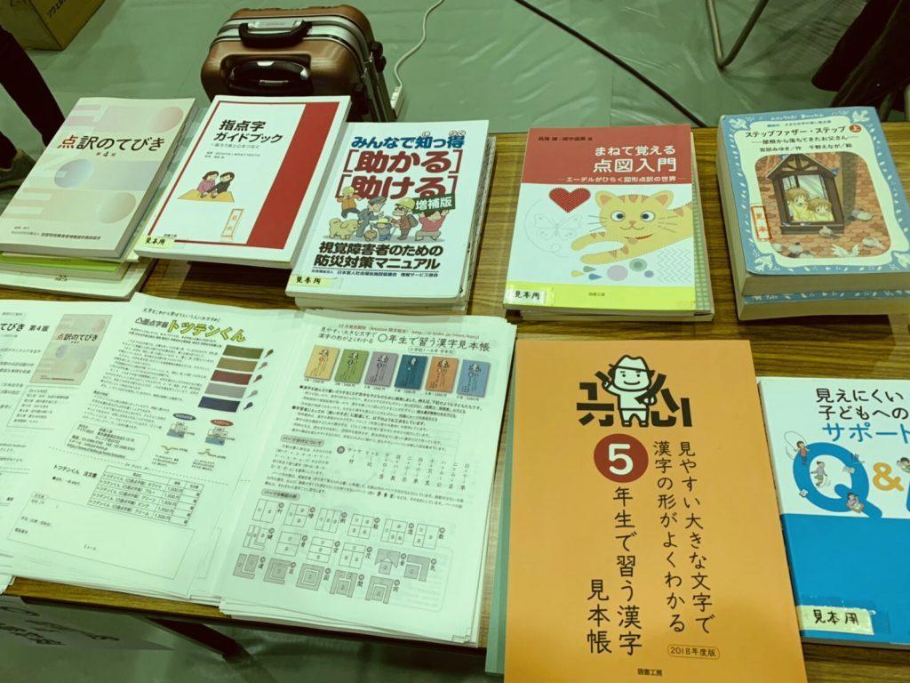 机の上に書籍がびっしりと並べられている画像