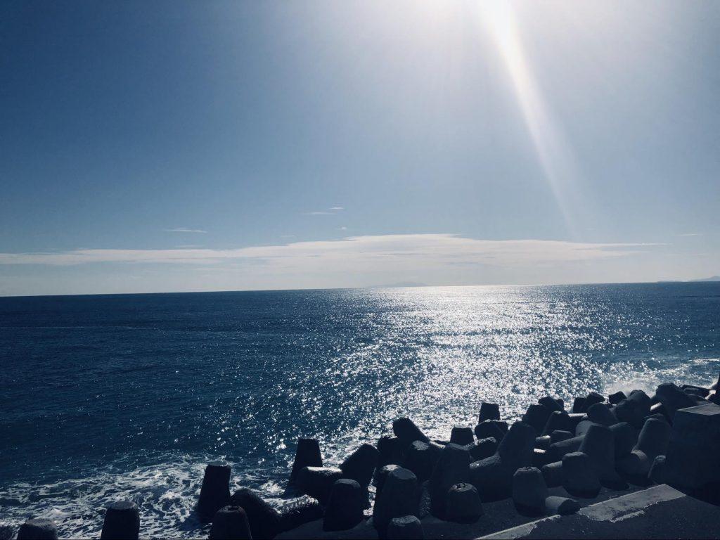 海岸から海を見渡している構図で、太陽の光が降り注いでいる画像