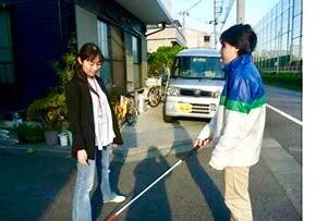 足を広げて訓練生に白杖のふり幅を伝える小倉さん