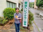 東京ヘレン・ケラー協会の看板の横に立つ小倉さん