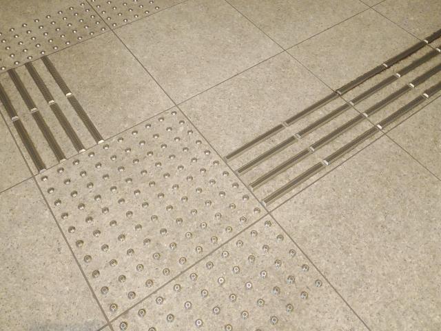 灰色のタイルの上に銀色の点字ブロックが敷設されている画像