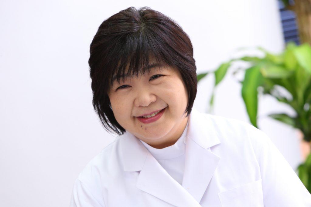 白衣を着た笑顔の椎野先生が斜め左を向いて微笑んでいる画像