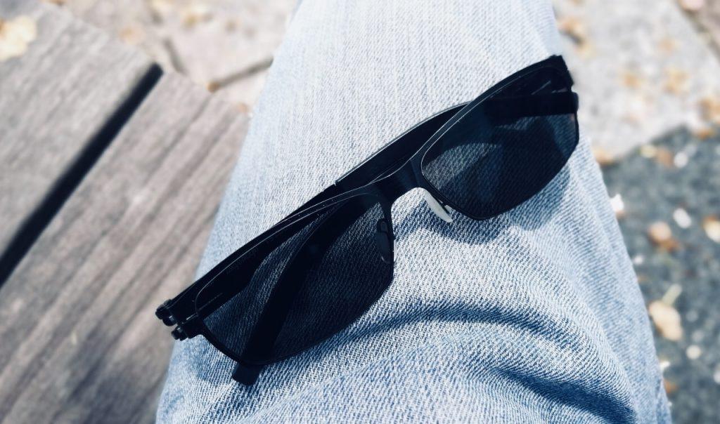 太ももの上に遮光眼鏡を置いている画像