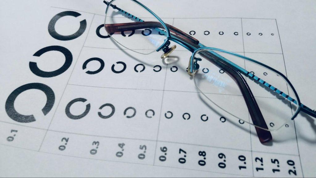 ランドルト環が書かれた視力検査表の上に眼鏡が置かれた画像