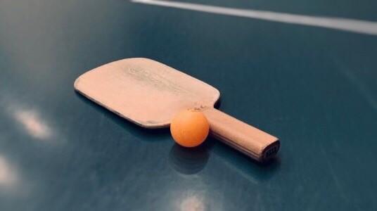 卓球台の上にラケットとボールが置かれている画像