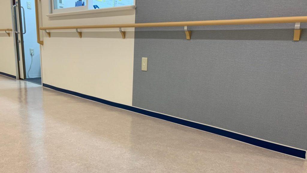白い壁とクリーム色の床の境目に、10㎝程度の青色の薄い板を貼っている画像。