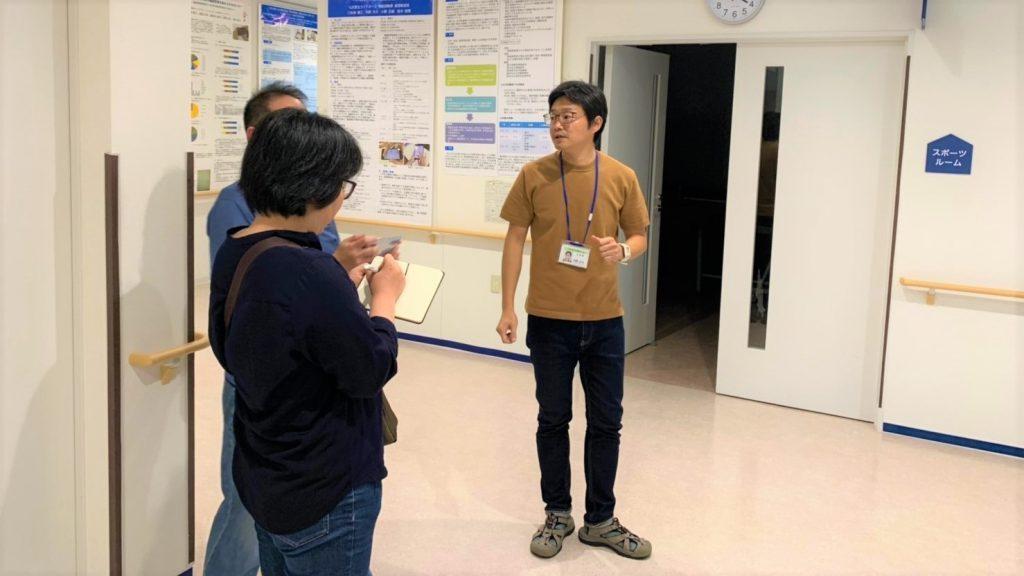 内野さんが施設の中を案内している画像。