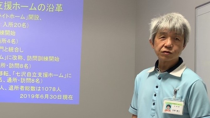 矢部さんがスライドを使い、施設の概要を説明している画像