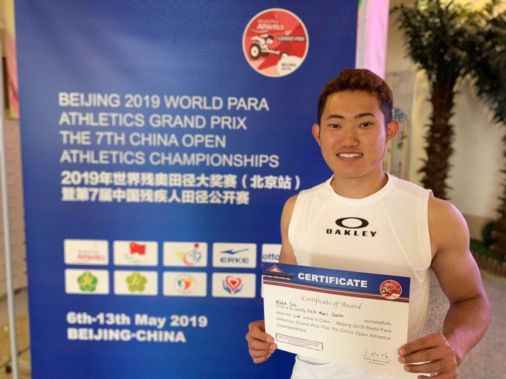 北京グランプリで記録証を持って記念撮影する若生くん