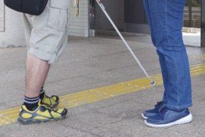 点字ブロックの上を歩く視覚障害者に声をかけている晴眼者を足元のみ撮影した画像
