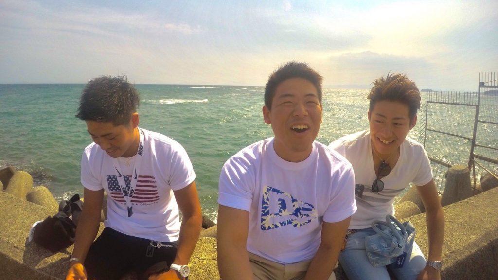 海を背に、友達ふたりと笑顔で写真に収まる山口さん