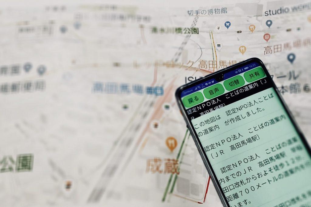 実際の地図の上に、ことばの道案内を開いたスマホを写している画像
