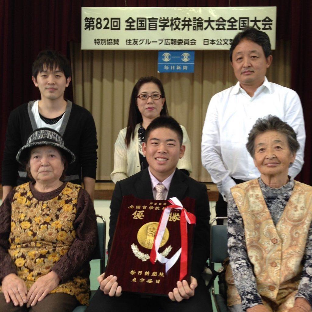全国盲学校弁論大会のあと、記念の盾を持って家族と記念撮影をする山口さん