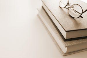 本が2冊重なった上に眼鏡を置いているレトロな画像