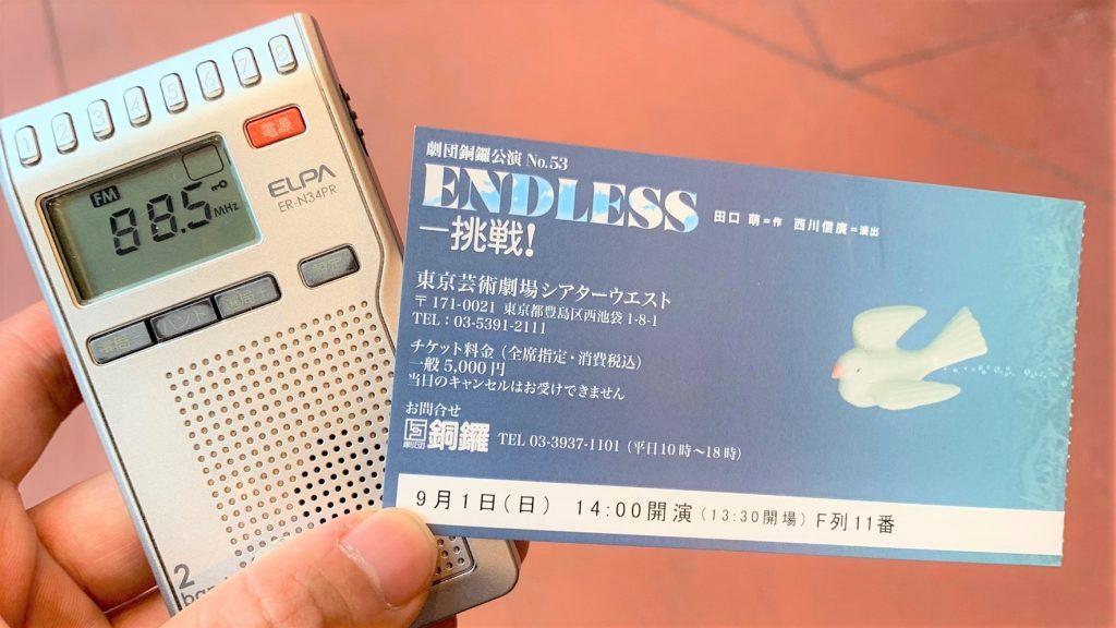 貸し出し用のポケットラジオとチケットを手に持っている画像。