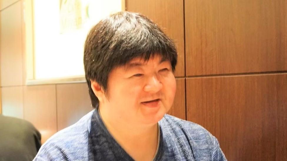 伊敷さんが笑顔で話をしている画像。