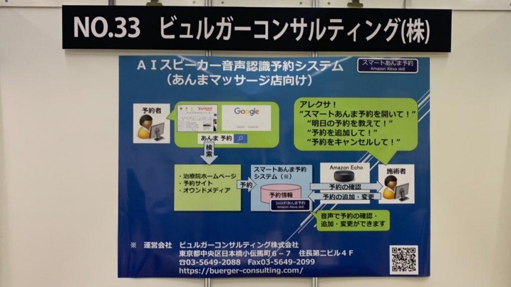 ブースの看板の下にシステムの概要を説明した紙が貼られている画像。