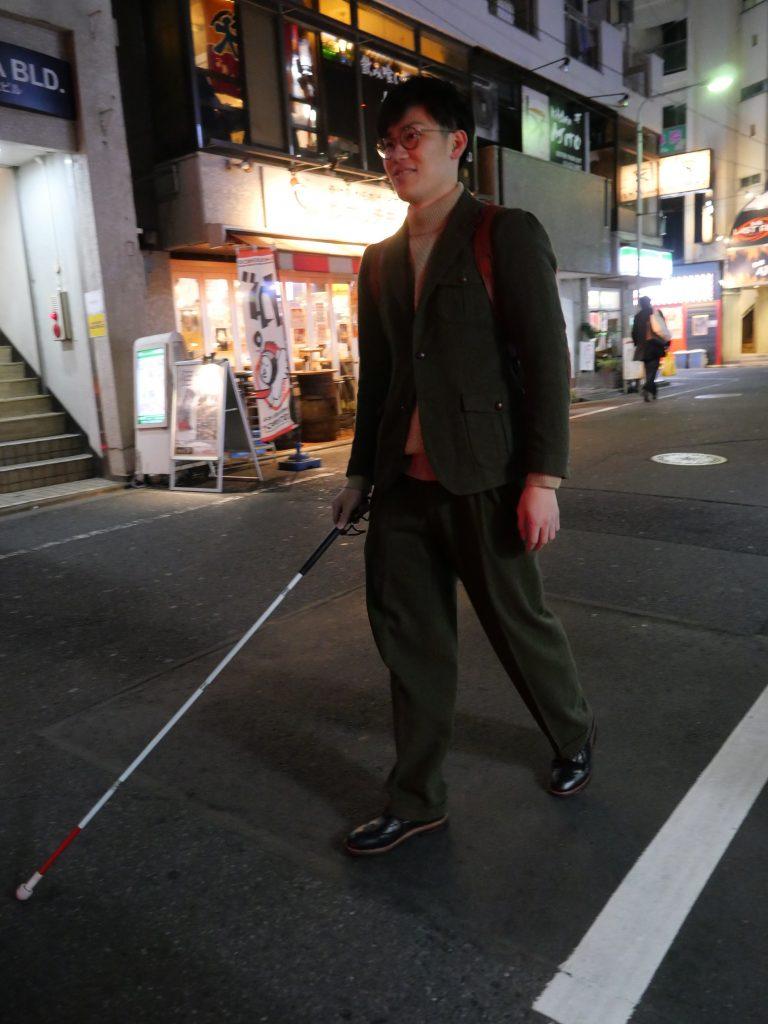 夜、人通りの少ない道を白杖を使って歩く宮食行次さん