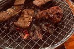 網の上で肉を焼いている画像