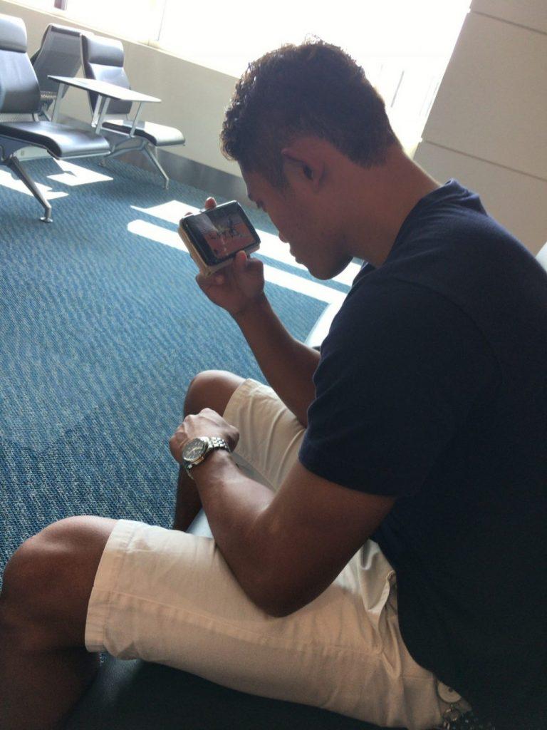 空港のロビーで、やり投げ選手の動画を見る若生くん