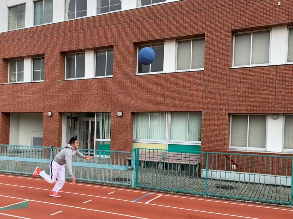 陸上競技場で、メディシンボールを投げ上げる若生くん