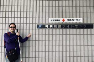 神奈川県ライトセンターの入り口にある看板を指さす渡辺敏之さん