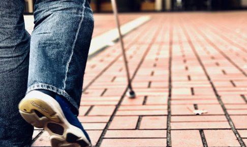 白杖を使って歩く渡辺さんを背後の足元から撮影した画像