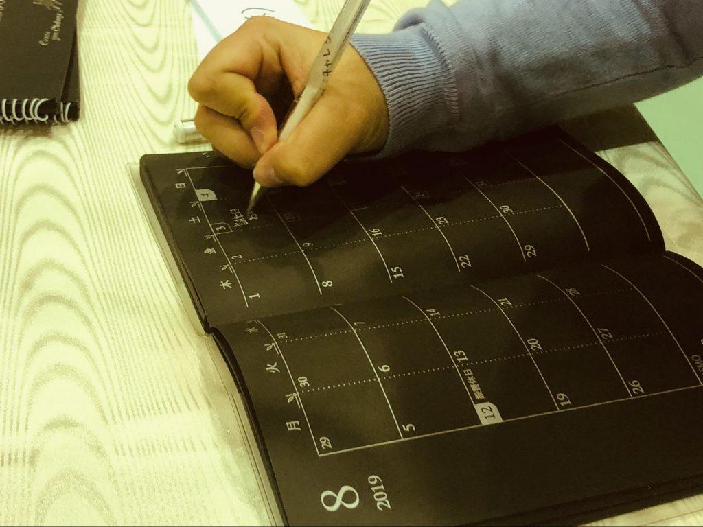 黒い手帳に白いボールペンで文字を書いている画像