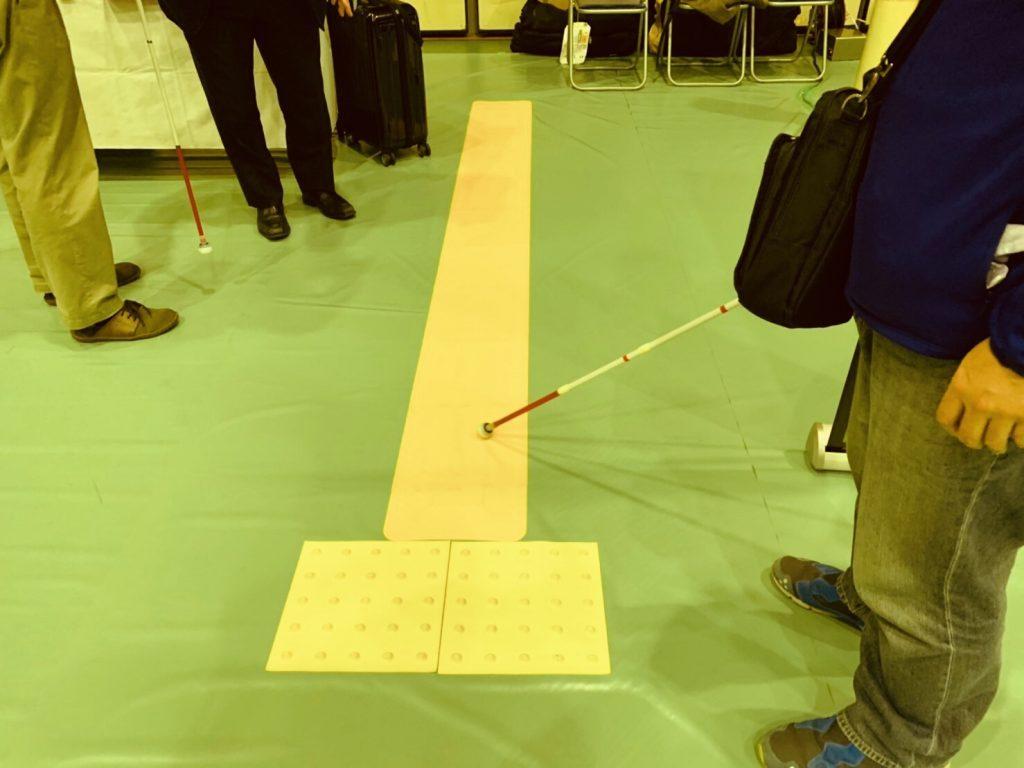 シートタイプの点字ブロックに白杖を沿わせている画像