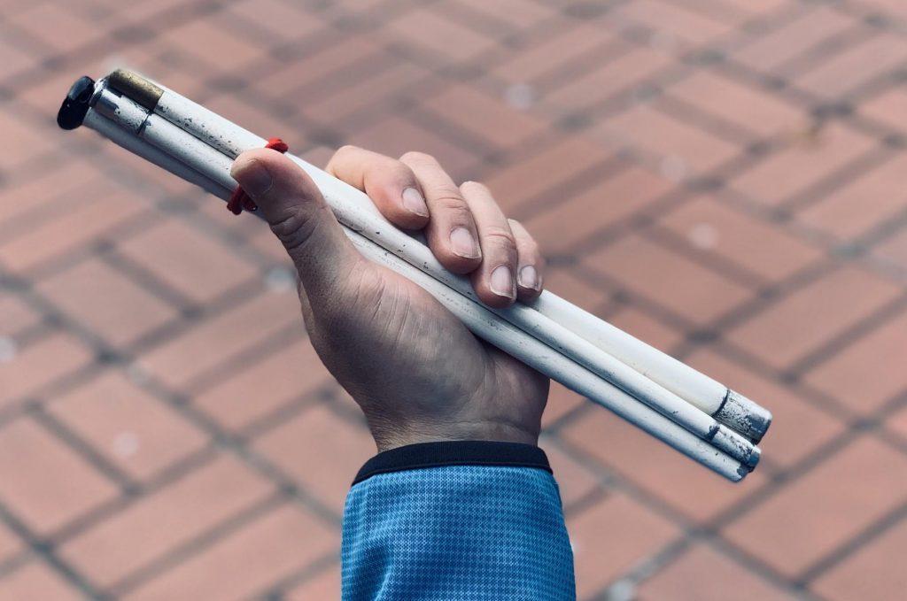 折り畳み式の白杖を手に持つ画像