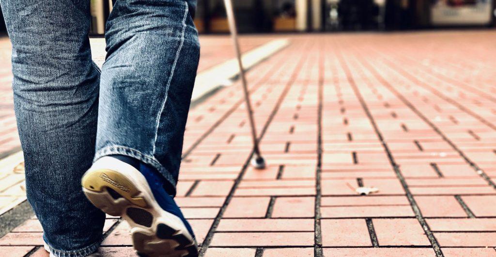 白杖を使って歩く視覚障害者の足元を背後から撮影したイメージ画像。