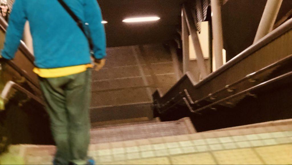 下り階段の手前で手すりを持って立ち止まる渡辺さん