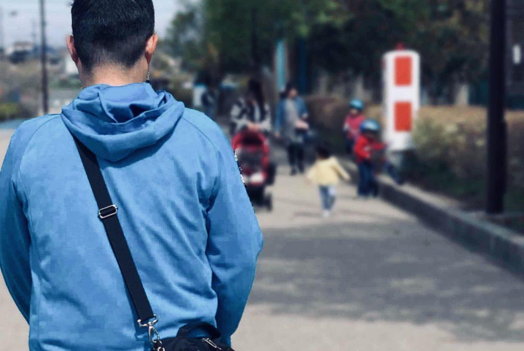 親子連れとすれ違う渡辺さんを背後から撮影した画像