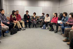円形に並んだ椅子に参加者が座っている画像