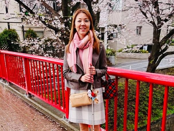 桜坂の橋の上で祈念撮影をする小林さん