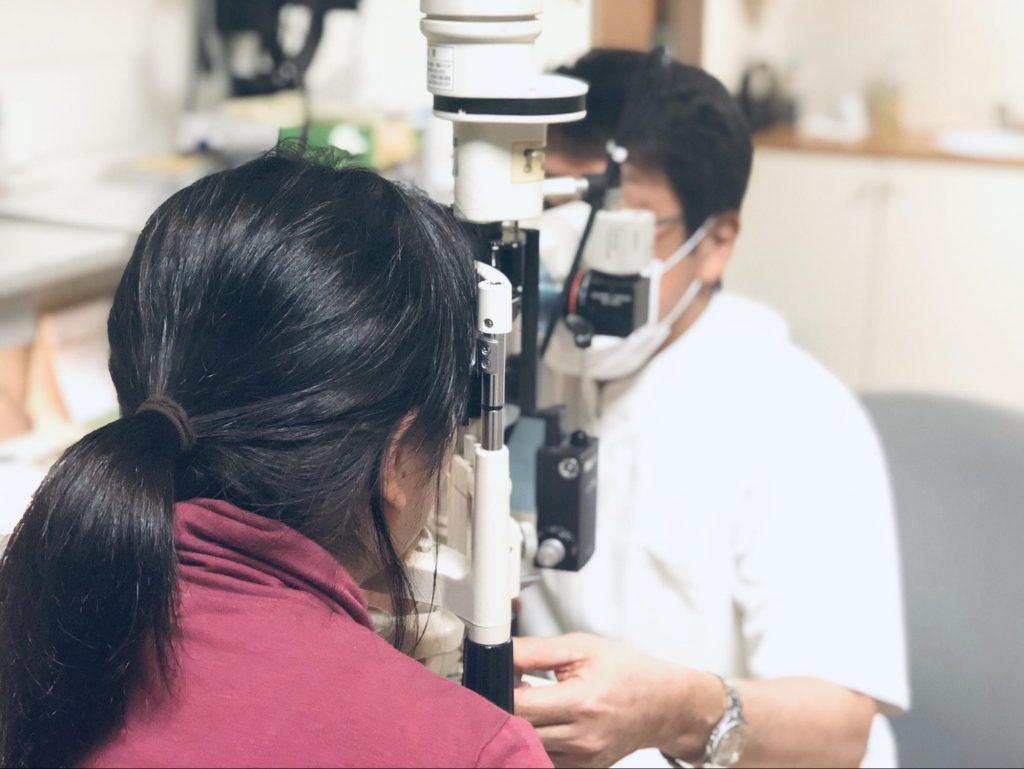 眼科の診察室で検査機に顔を乗せている下田さんを後ろから撮影した画像
