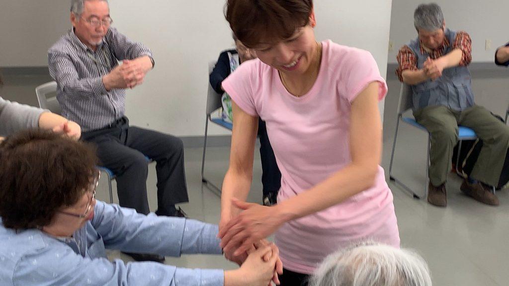 ヨガクラスで視覚障害者の身体に触れながら動きを伝える佐藤ゆみさん