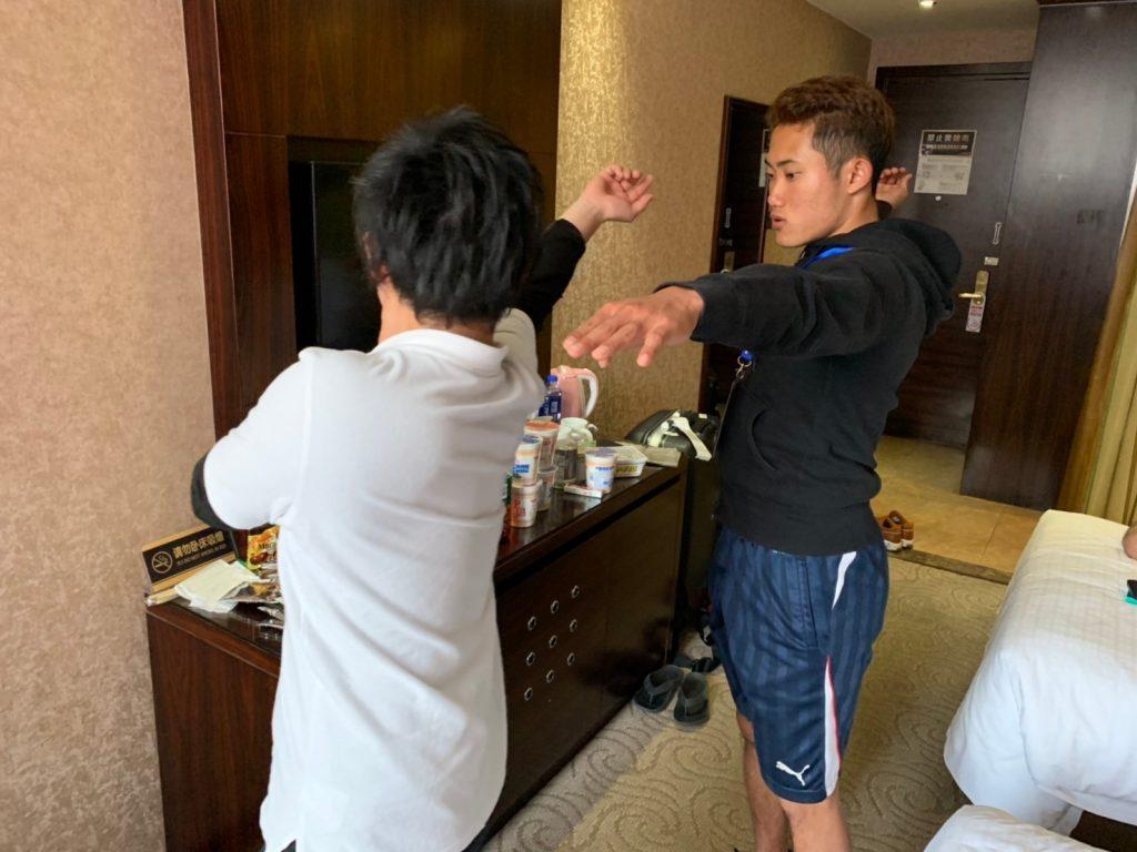 北京のホテルの部屋で、若生くんが田中さんのコーチからやり投げのフォームを教えてもらっている画像