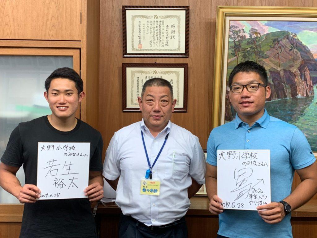 校長室で、若生くんと田中さんがサイン色紙を持ち、校長先生と記念撮影をしている画像