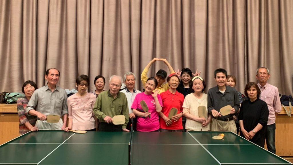 参加者全員が卓球台の後ろで記念撮影をしている画像