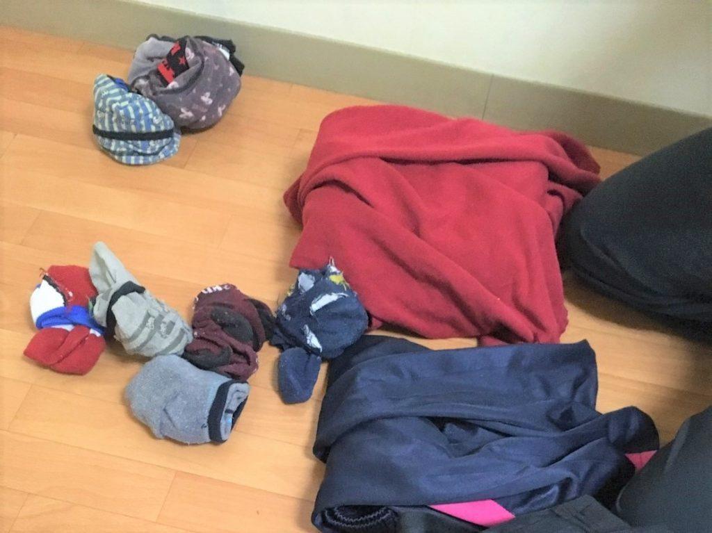 色々な色の靴下や服を畳んで収納する前の画像
