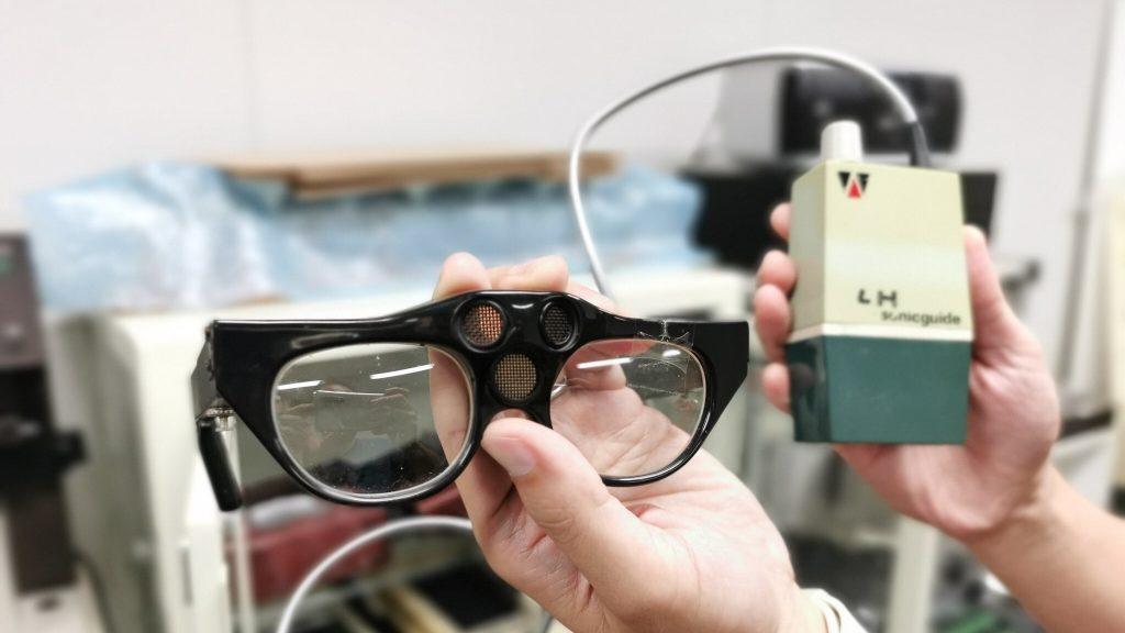 手の平サイズの四角いケースからコードでつながった眼鏡(ソニックガイド)を手に持って撮影した画像。