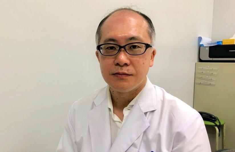 白衣を着た久米川先生の上半身を正面から撮影した画像