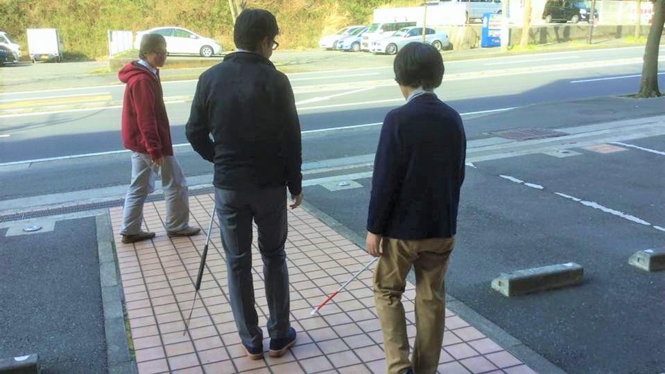 眼科の駐車場で、内野さんが患者に白杖の使い方を伝えている画像。