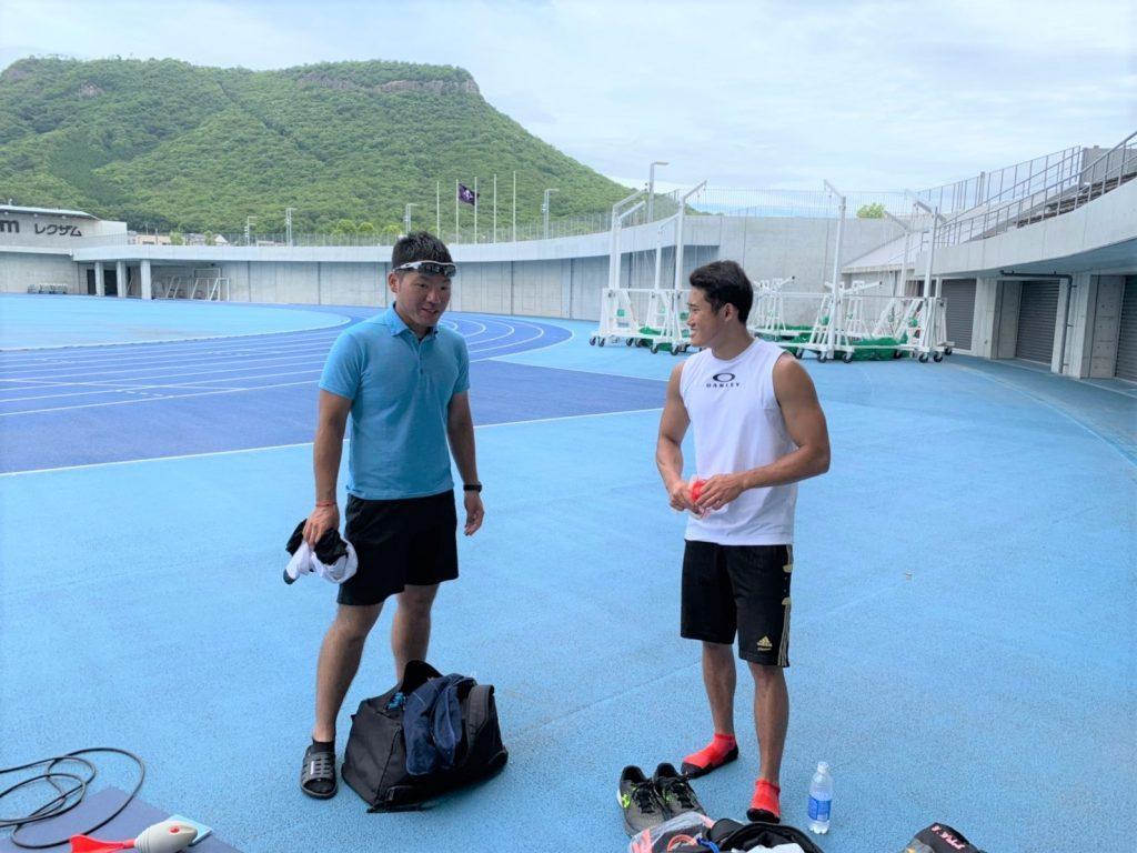 陸上競技場で田中さんと若生くんが談笑する画像